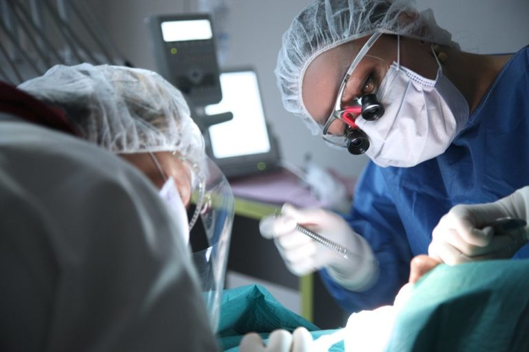 Dentist and assistant performing dental surgery on a patient